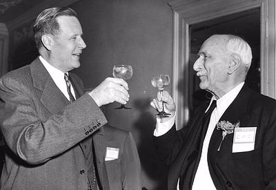 black and white photo of two men in suits toasting