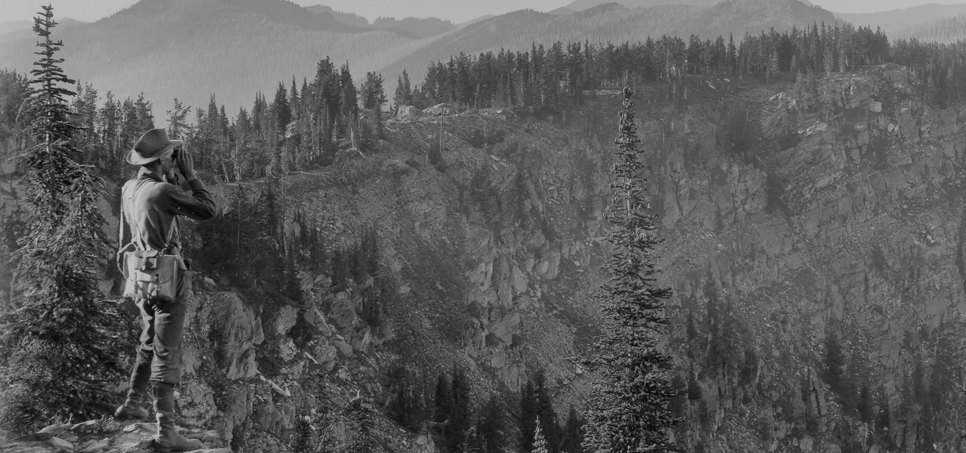 black and white photo of ranger looking over a rocky mountain valley