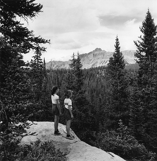 black and white photo of two middle school aged children looking out over a mountain scape