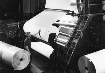 black and white photo of paper rolls on large machine