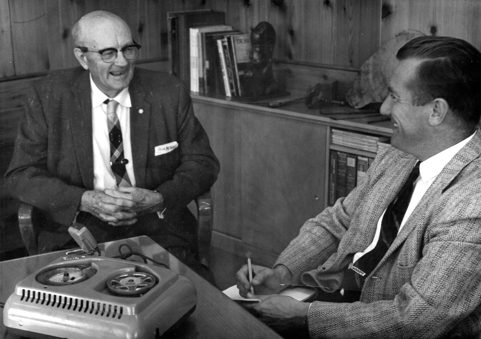 black and white photo of two men sitting and talking