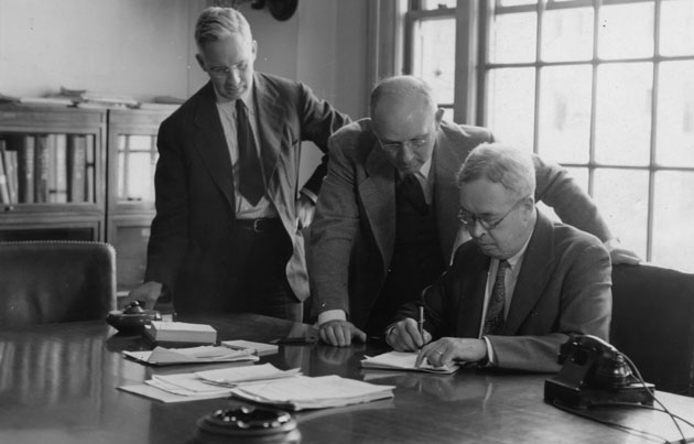 Image of Earl S.  Pierce, Harry Joseph, and Earle H. Clapp signing a timber salvage sales agreement following the 1938 New England Hurricane. Click for more information.