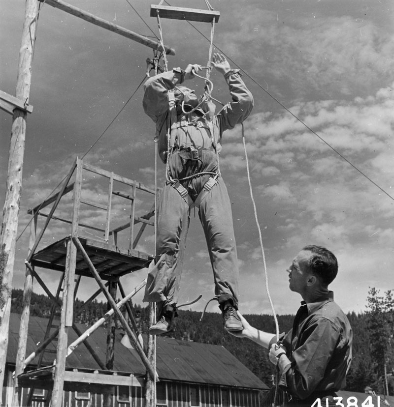 Frank Derry, parachute instructor-rigger, instructing prospective smokejumper.