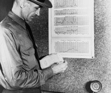 Harry Gisborne studying printouts of fire risk factors, Priest River Forest Research Station, Idaho, 1937.