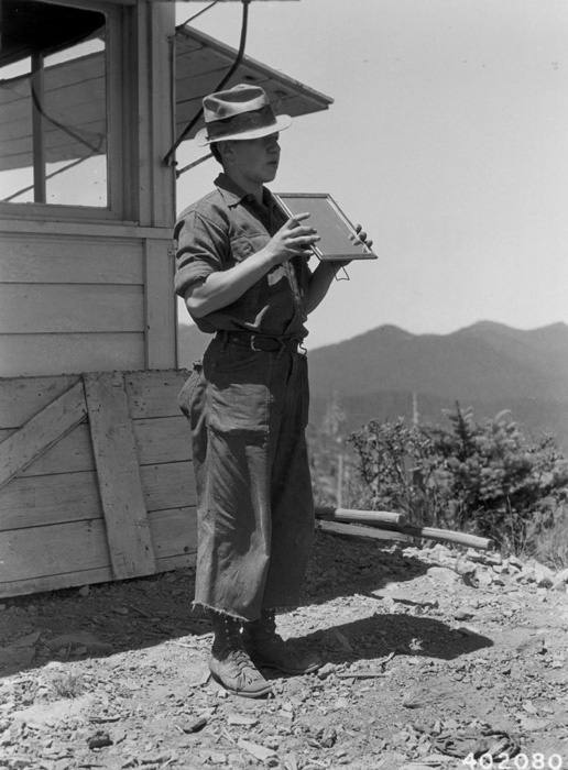 Fire lookout signals with handheld mirror.