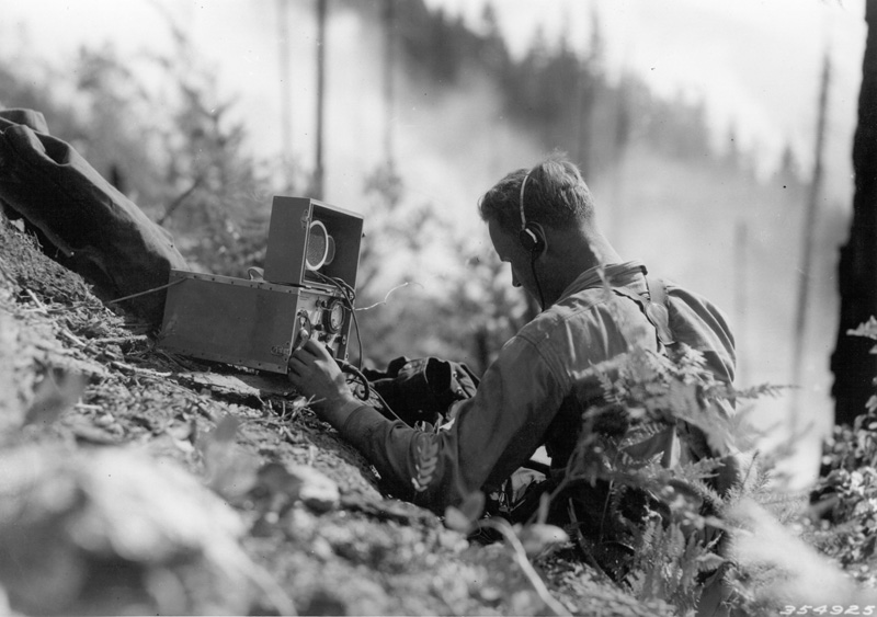 Forest Service technician operating emergency radio station on hillside during Spud Hill Fire.