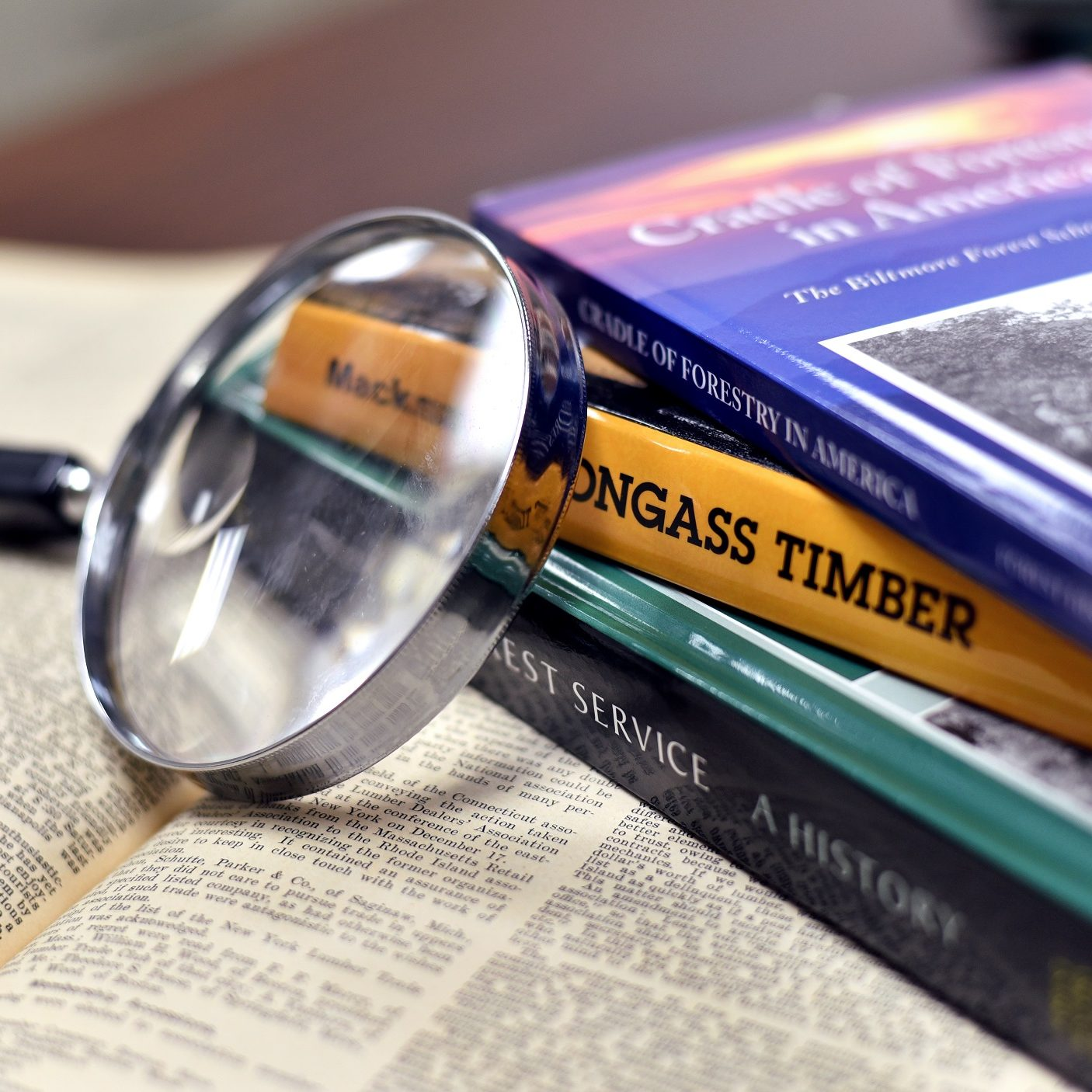 books with magnifying glass