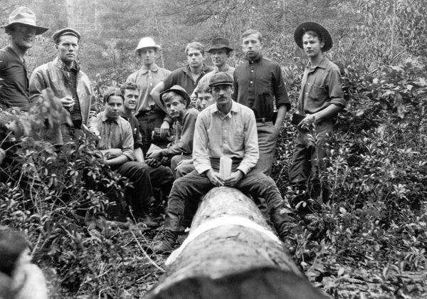 black and white photo of forester students sitting on and standing around a downed tree